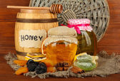 Jars of honey, wooden barrel, drizzler and dried fruits on wooden background — Stock Photo