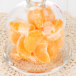 Tangerine on saucer under glass cover on light background — Stock Photo #22920770