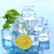 Ice cubes with mint and lime on light blue background — Stock Photo #22923490