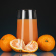 Delicious tangerine juice in glass and mandarins next to it on dark blue background — Stock Photo #22924002