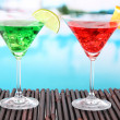 Glasses of cocktails on table near pool — Stockfoto