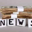 Foto Stock: White paper cubes labeled News with money on grey background