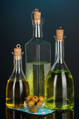 Original glass bottles with oil on dark color background — Stock Photo