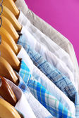 Men's shirts on hangers on purple background — Stock Photo