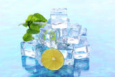 Ice cubes with mint and lime on light blue background — Stock Photo