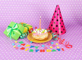 Colorful birthday cake with candle and gifts on pink background — 图库照片