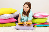 Beautiful young girl with pillows and book in room — Stock Photo