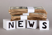 White paper cubes labeled News with money on grey background — Stock fotografie