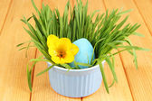 Easter egg in bowl with grass on wooden table close up — Stock Photo