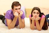 Jeune couple allongé sur la moquette à la maison — Photo