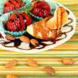 Fruit in chocolate on plate on tablecloth close-up — Stockfoto