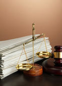 Golden scales of justice, gavel and folders on brown background — Stock Photo