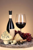 Refinado ainda vida de vinho, queijo e uvas na bandeja de vime na mesa de madeira no fundo bege — Fotografia Stock