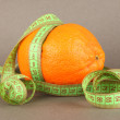 Orange with measuring tape, on color background — Stock Photo