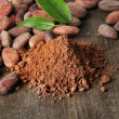 Cocoa beans and cocoa powder on wooden background — Stock Photo #22949708
