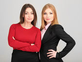 Two business women on grey background — Stock Photo