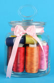Glass jar containing various colored thread on blue background — Stockfoto
