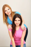 Two girl friends hugging on grey background — Stock Photo