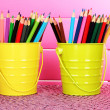 Colorful pencils in two pails on table on pink background — Stock Photo #22967102