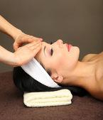 Beautiful young woman in spa salon taking head massage, on dark background — Stock Photo
