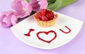 Söt tårta med jordgubbar och sås på plattan, cologne bakgrunden — Stockfoto