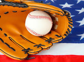 Baseball glove and ball on American flag background — Stock Photo