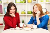 Twee meisje vrienden praten en drinken thee in keuken — Stockfoto