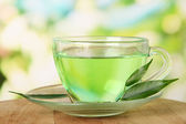 Transparent cup of green tea, on nature background — Stock Photo