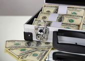 Suitcase with 100 dollar bills on grey background — Stock Photo