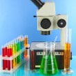 Test tubes with colorful liquids and microscope on blue background - Stock Photo