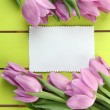 Stock Photo: Beautiful bouquet of purple tulips and blank card on green wooden background