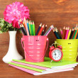 Colorful pencils in pails with copybooks on wooden background — Stock Photo