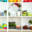 Beautiful white shelves with tableware and deco — Stock Photo
