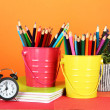 Colorful pencils in two pails with copybooks on table on orange background — Stok fotoğraf