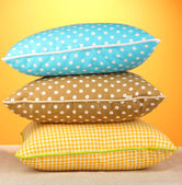 Brown, yellow and blue bright pillows on orange background — Stockfoto