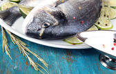 Two fish dorado with lemon on plate on blue wooden table close-up — Stock Photo