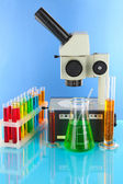 Test tubes with colorful liquids and microscope on blue background — Stock Photo