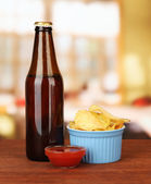 Potato chips and glass bottle with beverage, on bright background — Stock Photo
