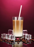 Cold coffee with ice in glass on color background — Stock Photo