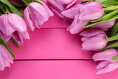Beautiful bouquet of purple tulips on pink wooden background — Stok fotoğraf