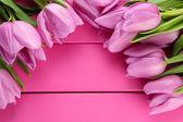 Piękny bukiet tulipanów fioletowy na różowym tle drewniane — Zdjęcie stockowe