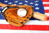 Baseball glove, bat and ball on American flag background — Stock Photo