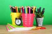 Colorful pencils with school supplies on table on green background — Stock Photo