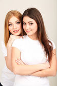 Two girl friends smiling on grey background — Stock Photo