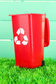 Recycling bin on grass on light blue background — Stock Photo