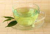 Transparent cup of green tea on bamboo mat, close up — Stock Photo
