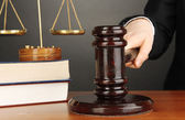 Judge's gavel in hand on grey background — Stock Photo