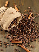 Coffee in sack on wooden table — Stock Photo