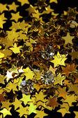 Beautiful shining crystals (diamonds) on golden stars background — Stock Photo