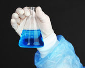 Glass tube with fluid in scientist hand during medical test on black background — Stockfoto
